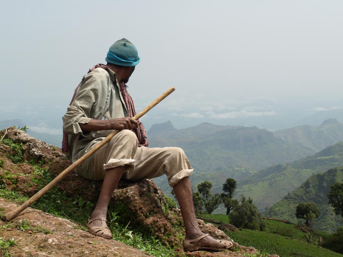 Un hombre sentado mirando un valle a sus espaldas