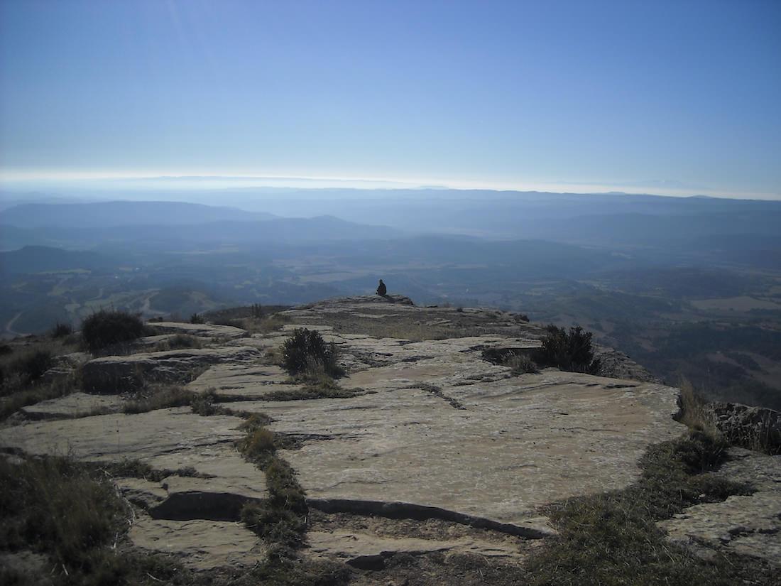 un imenso cielo azul y una imagen humana sentada en el borde de un precipicio.